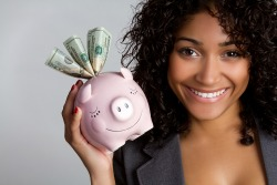 African american woman holding piggy bank