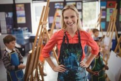 Portrait of smiling teacher standing with hands on hip in drawing class